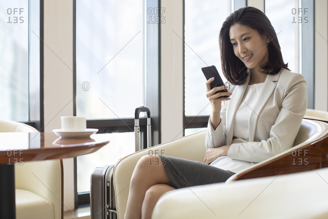 Confident Chinese businesswoman using smartphone in airport lounge