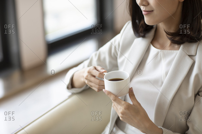 Confident Chinese businesswoman drinking coffee in coffee shop