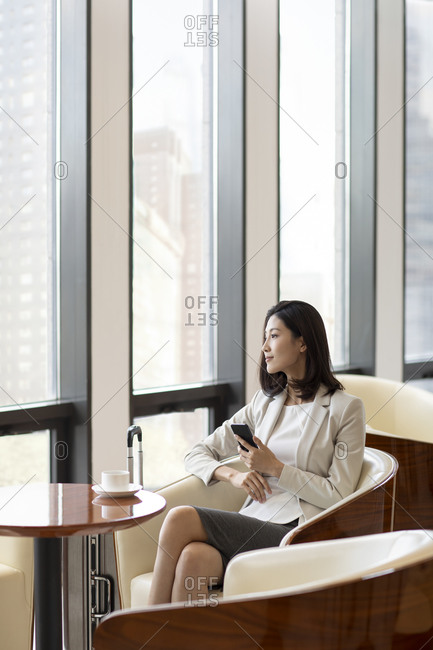 Confident Chinese businesswoman waiting in airport lounge