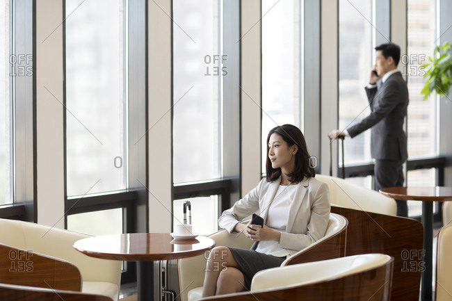 Confident Chinese business people waiting in airport lounge