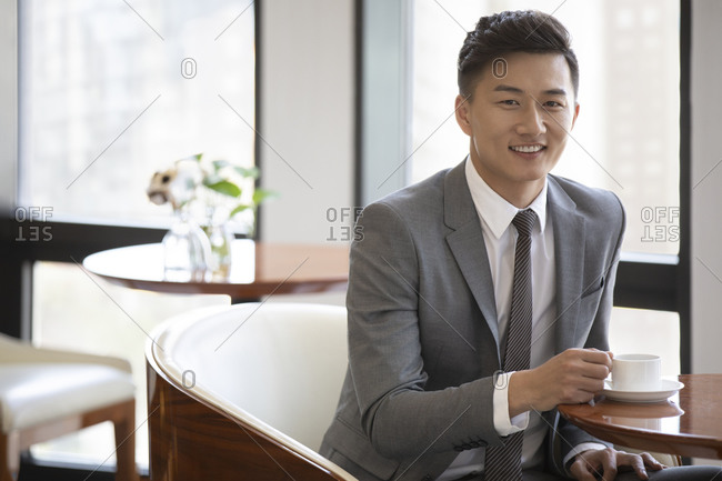 Confident Chinese businessman drinking coffee in coffee shop