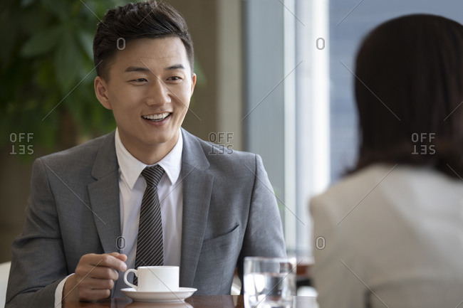 Confident Chinese business people talking in coffee shop