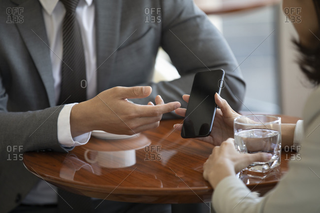 Confident Chinese business people using smartphone in coffee shop