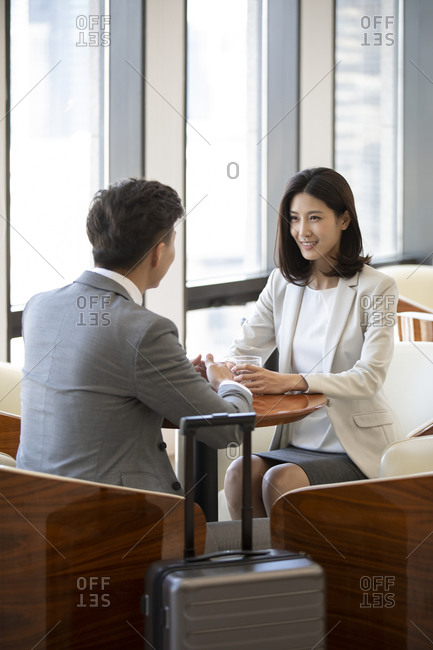 Confident Chinese business people talking in airport lounge