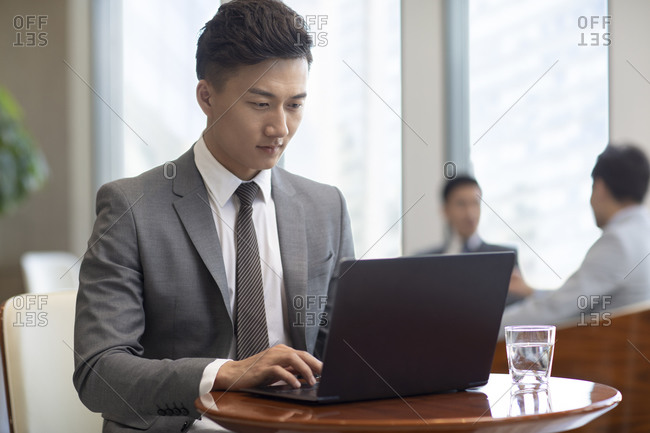Confident Chinese businessman using laptop in coffee shop