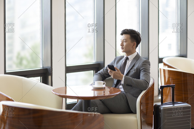 Confident Chinese businessman drinking coffee in airport lounge