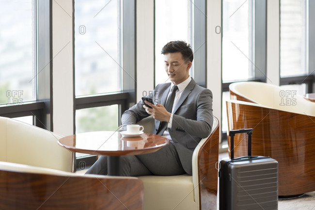 Confident Chinese businessman using smartphone in airport lounge