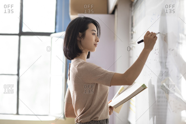 Young Chinese teacher writing on blackboard
