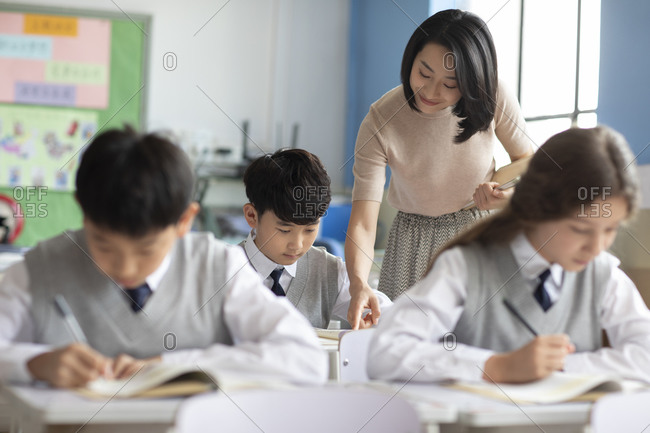 Young Chinese teacher helping students in classroom