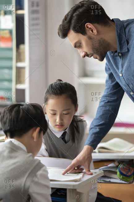 Young teacher helping students in classroom