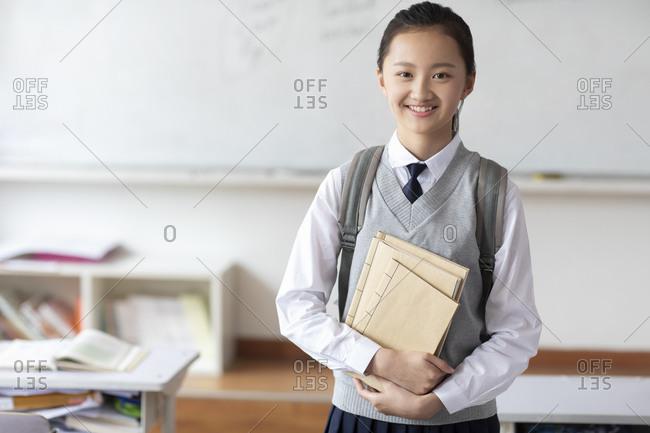 Chinese schoolgirl standing in classroom