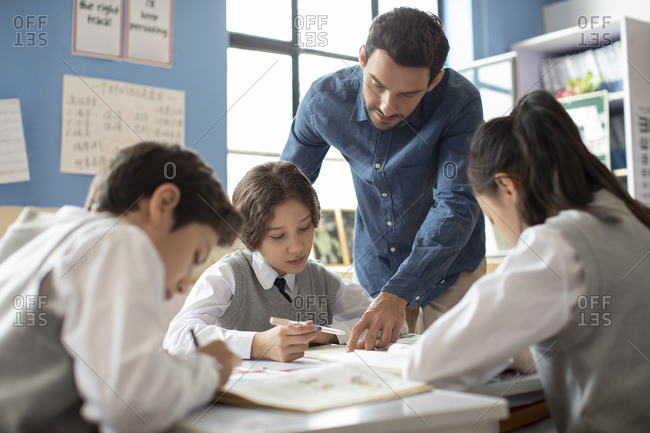 Students learning from teacher in classroom