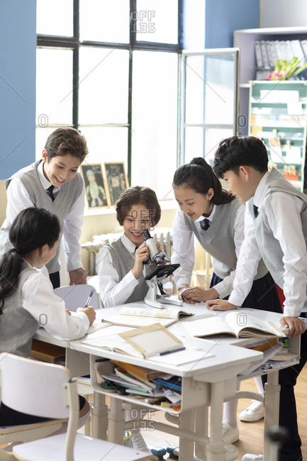 Students using microscope in classroom