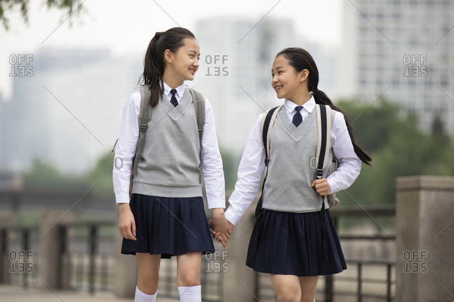 Chinese schoolgirls walking hand in hand on campus