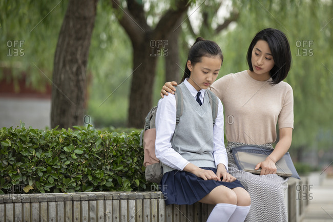 Chinese teacher consoling student outside