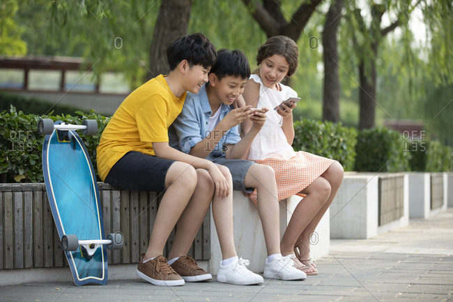 Teenagers using smartphone outdoors together