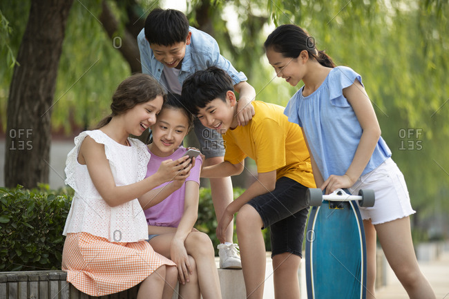 Teenagers having fun on their smartphones outdoors