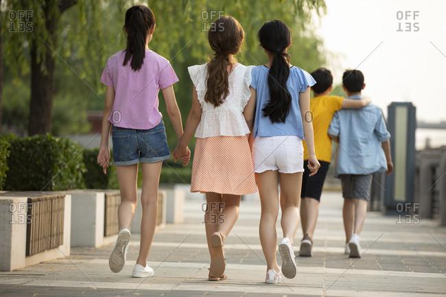 Teenagers having fun outdoors, from behind