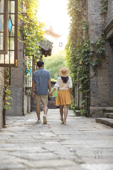 Young Chinese couple walking in alley