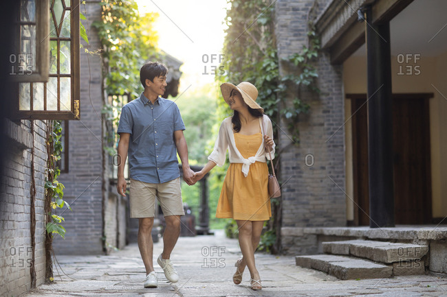 Happy young Chinese couple walking in alley