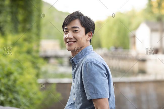 Happy young Chinese man enjoying vacation