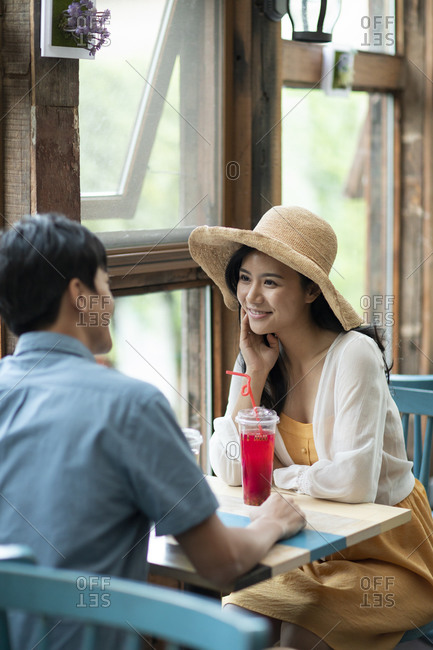 Happy young Chinese couple drinking cold drink in store
