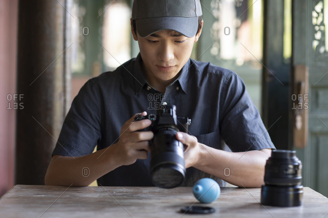 Young Chinese photographer examining photos on camera