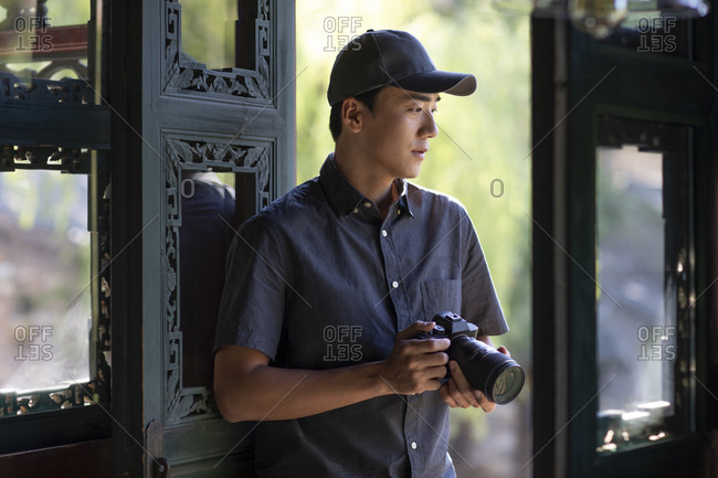 Young Chinese photographer using camera
