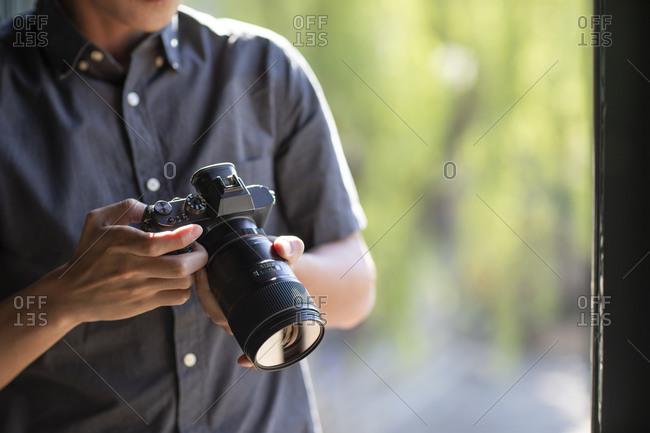 Young Chinese photographer examining photos on camera