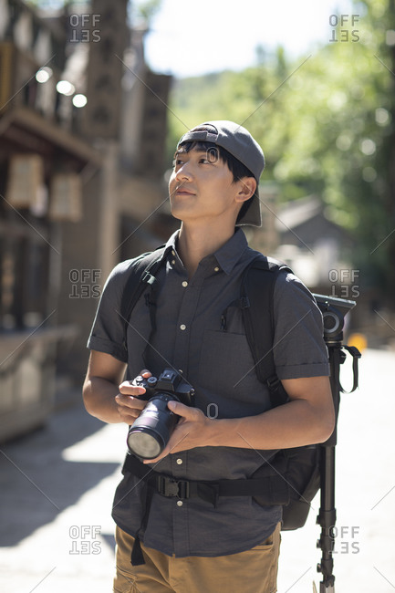 Young Chinese photographer taking photos with camera