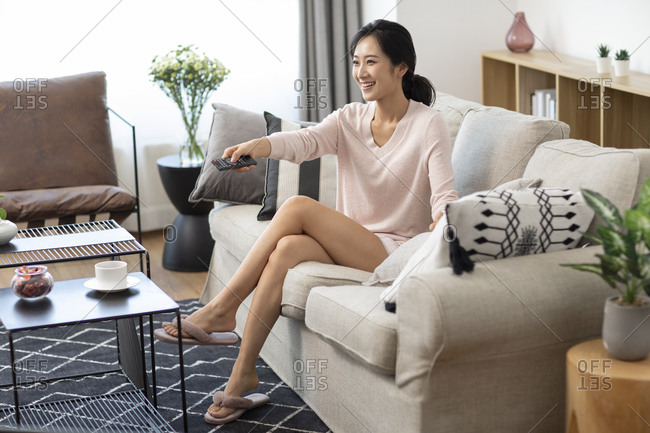 Happy young Chinese woman watching TV in living room