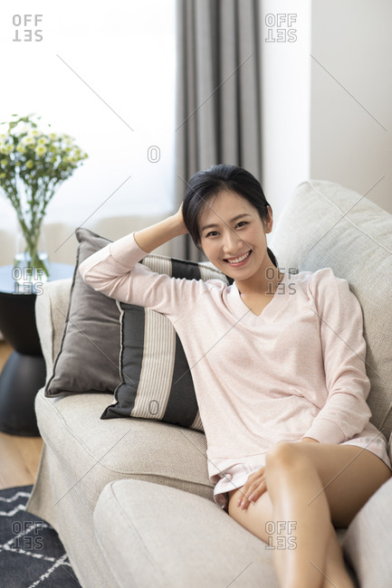 Happy young Chinese woman resting on sofa