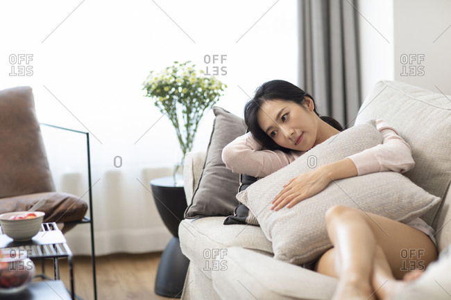 Unhappy young Chinese woman on sofa