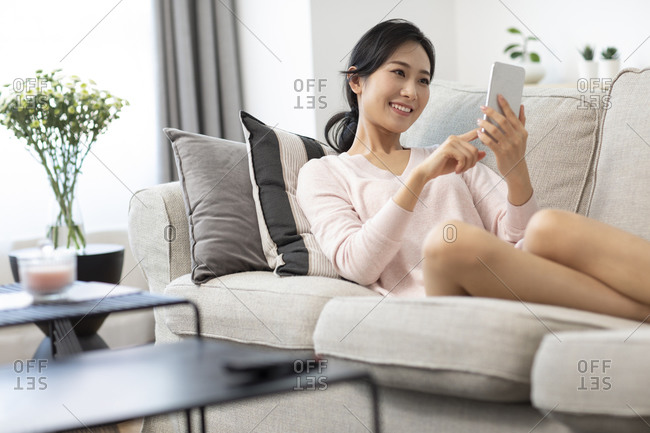 Happy young Chinese woman using smartphone in living room