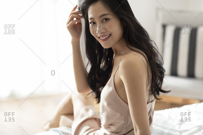 Happy young Chinese woman waking up in the morning