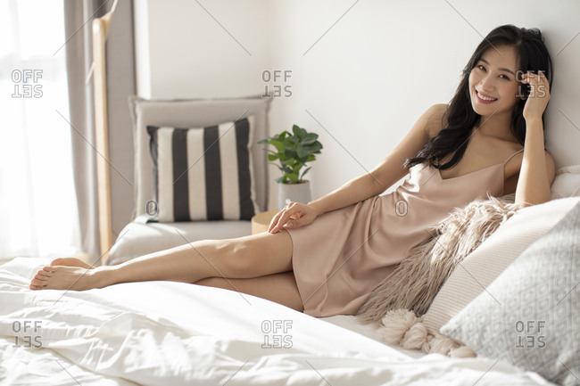 Happy young Chinese woman relaxing on bed