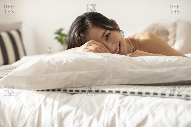 Happy young Chinese woman lying on bed
