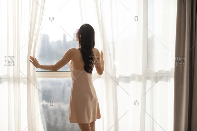Young Chinese woman opening curtains in the morning