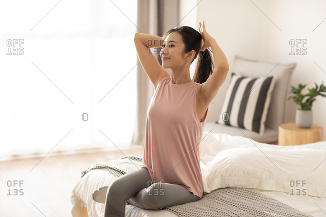 Happy young Chinese woman getting ready for morning exercise
