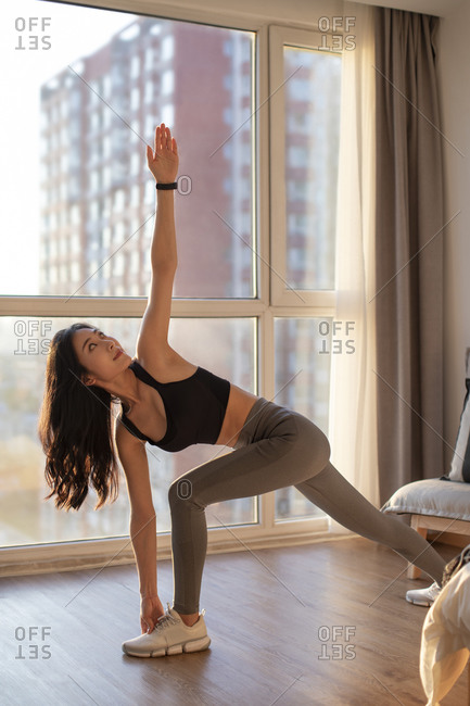 Happy young Chinese woman exercising at home