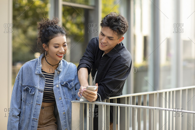 Fashionable young Chinese couple using smartphone on street
