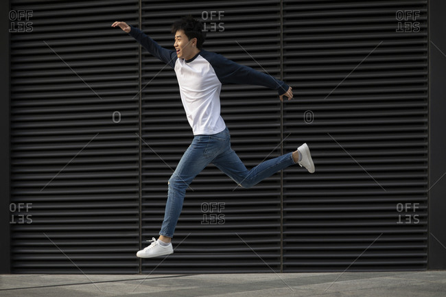 Happy young Chinese man jumping in the air