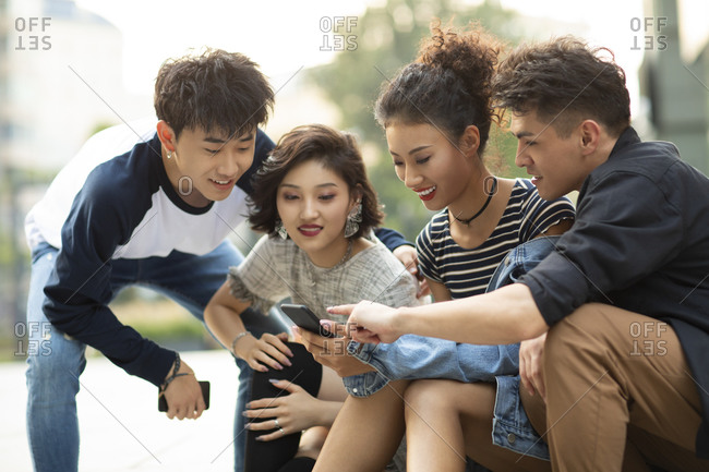 Happy young Chinese friends using smartphone outdoors