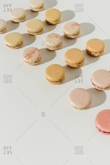 Macarons arranged in rows on white surface