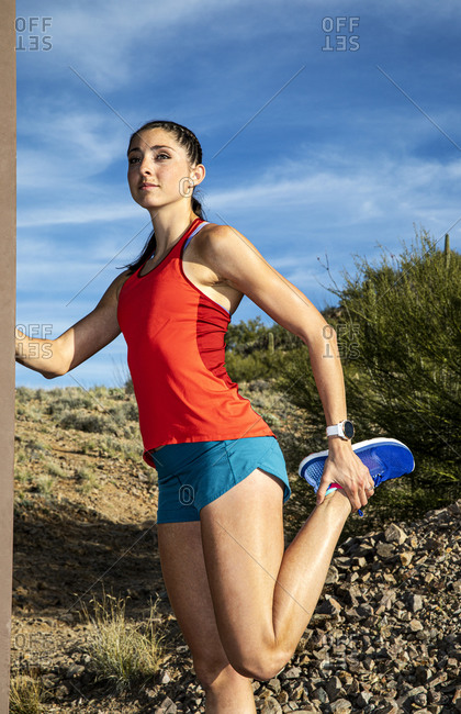 Young athletic woman stretching her legs before a run