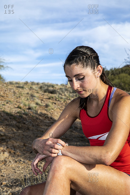 Young athletic woman checking her watch before a run