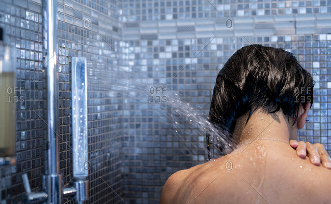 Woman taking shower, from behind