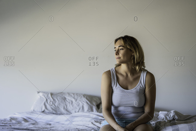 Woman sitting on bed in summer clothes