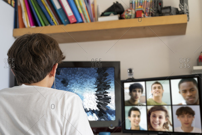 Teenage boy video chatting on the computer with friends at home