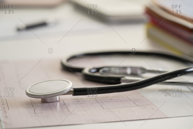 Stethoscope on top of medical report